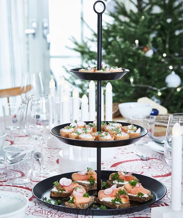 Plats de présentation avec hors-d'œuvre délicats, sur une table dressée pour un festin. Arbre de Noël à l'arrière-plan.
