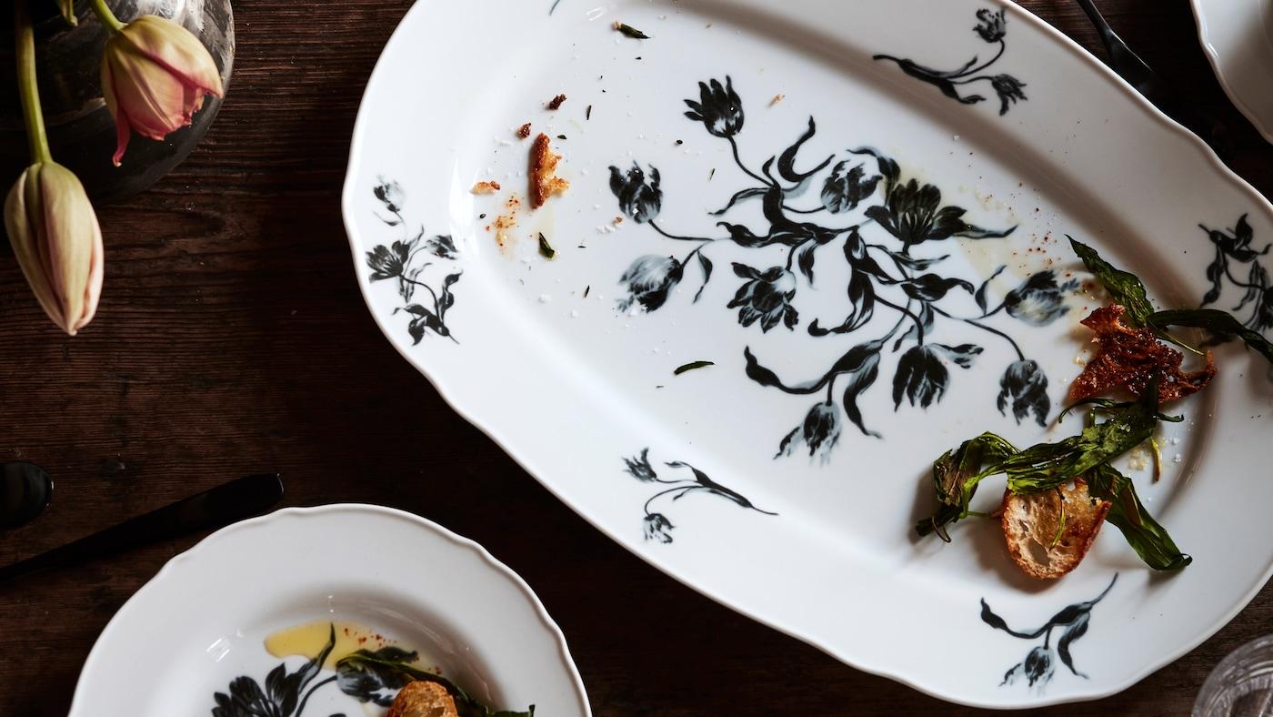 Plats de servir i platets UPPLAGA de color blanc amb un estampat floral, que contenen menjar sobrant, col·locats sobre una taula de fusta amb tulipes.