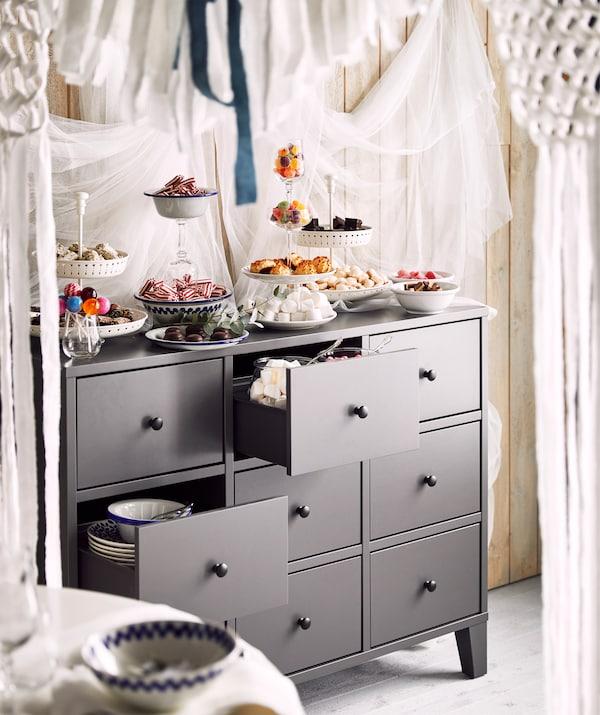 Plats et verres remplis de friandises et de biscuits déposés sur une commode grise. Les tiroirs sont aussi mis à contribution.