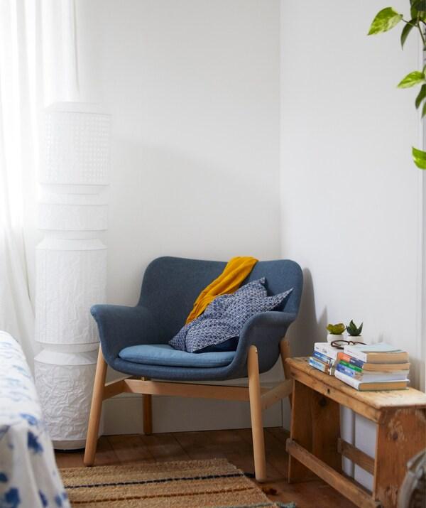 Plava fotelja u uglu bele prostorije i podna lampa s papirnim abažurom.