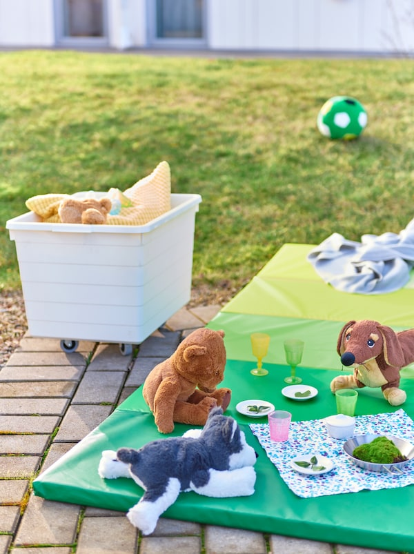 Playful dinner for a circle of soft-toys animals on a PLUFSIG mat by a patch of grass. A SOCKERBIT box with more toys nearby.