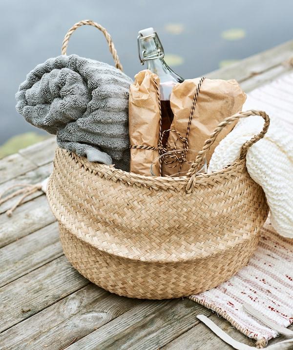Pletena košara spakirana za piknik sa smotanim sivim ručnikom, sendvičima umotanim u papir, kremastom laganom dekom i bocom pića.