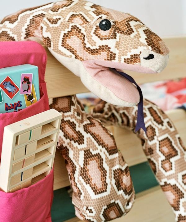 Plišani piton obmotan oko okvira drvenog kreveta, pored dodatnog platnenog džepa za odlaganje, punog knjiga.