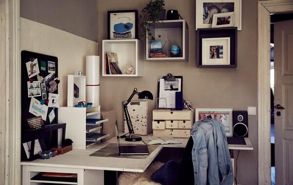 Plitka fioka za pisma i kutije na ugaonom radnom stolu s kockastim elementima za odlaganje na zidu iznad.
