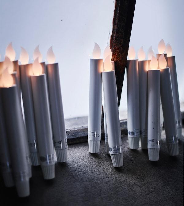 Plusieurs bougies à DEL fonctionnant à piles appuyées contre la fenêtre