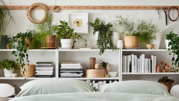 Plusieurs cache-pots contiennent des plantes réelles et artificielles parmi des livres et des décorations sur des étagères près d'un lit fait avec un linge de lit BERGPALM.