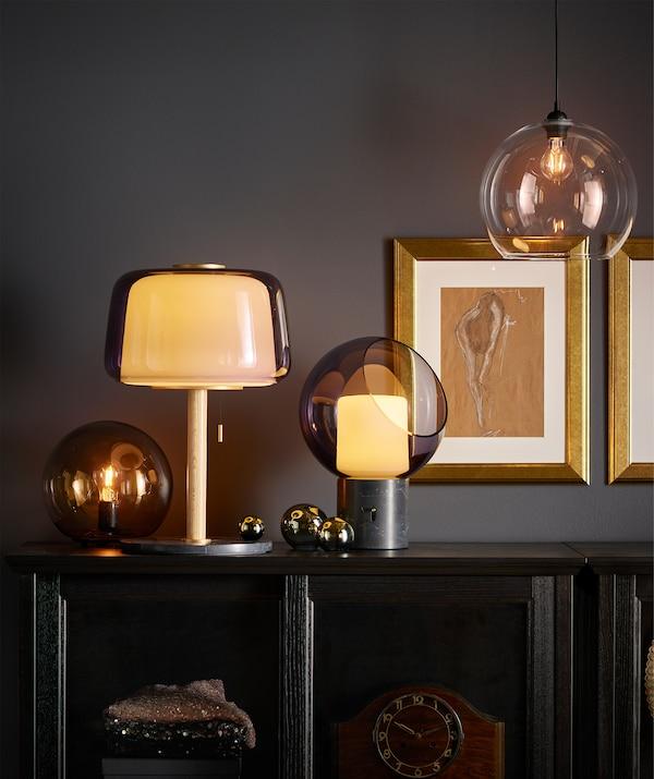 Plusieurs lampes de table placées sur un meuble de rangement dans une salle de séjour; la plupart de celles-ci sont en verre gris et dégagent une lumière jaune et chaude.