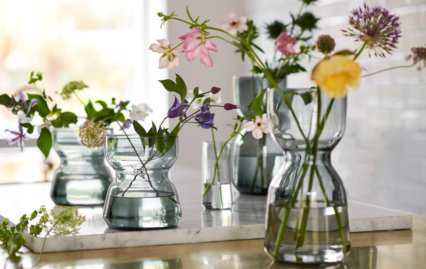 Plusieurs vases en verre OMTÄNKSAM, aux courbes caractéristiques pour faciliter la prise en main, sur un plan de travail, remplis de fleurs fraîchement coupées.
