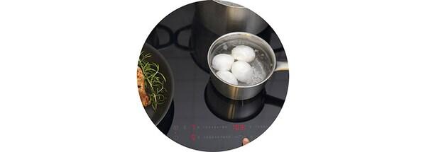 Płyta indukcyjna IKEA z garnkiem IKEA, w którym gotują się jajka.