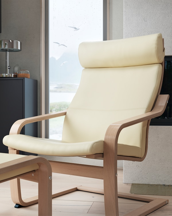 POÄNG armchair in white stained oak veneer with stylish eggshell cover, together with a footstool and in front of a window.