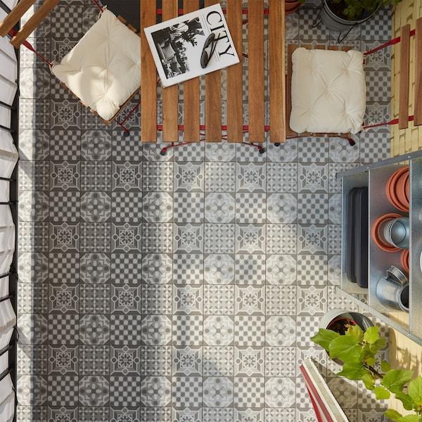 Podeaua de exterior MÄLLSTEN cu modele gri/albe, o masă și scaune din lemn roșu/maro deschis băițuit și o etajeră.