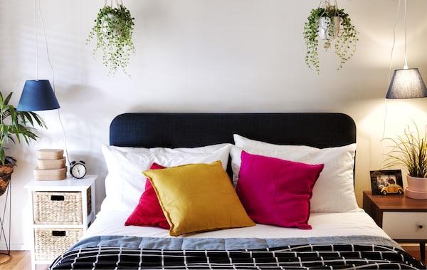 Podwójne łóżko z kolorowymi poduszkami i ułożoną warstwami pościelą, z dwoma stolikami nocnymi, lampami wiszącymi i wiszącymi kwietnikami.
