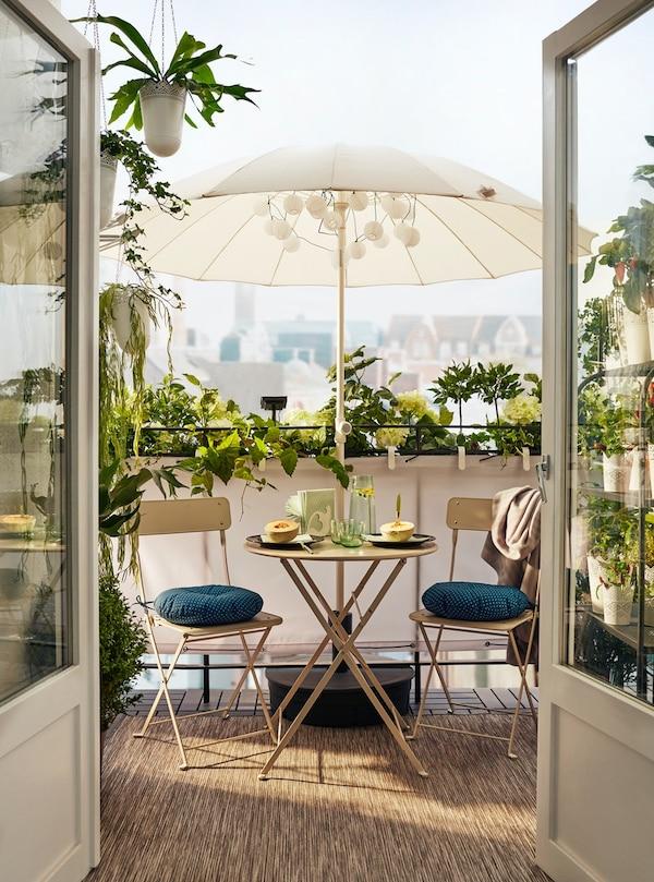 Podwójne szklane drzwi otwierają się na balkon otoczony roślinami i wyposażony w stół dla dwojga pod beżowym parasolem.