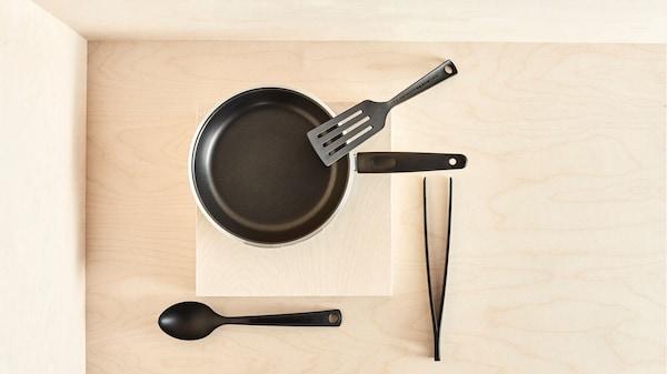poele-et-ustensiles-de-cuisine-noir-sur-fond-beige