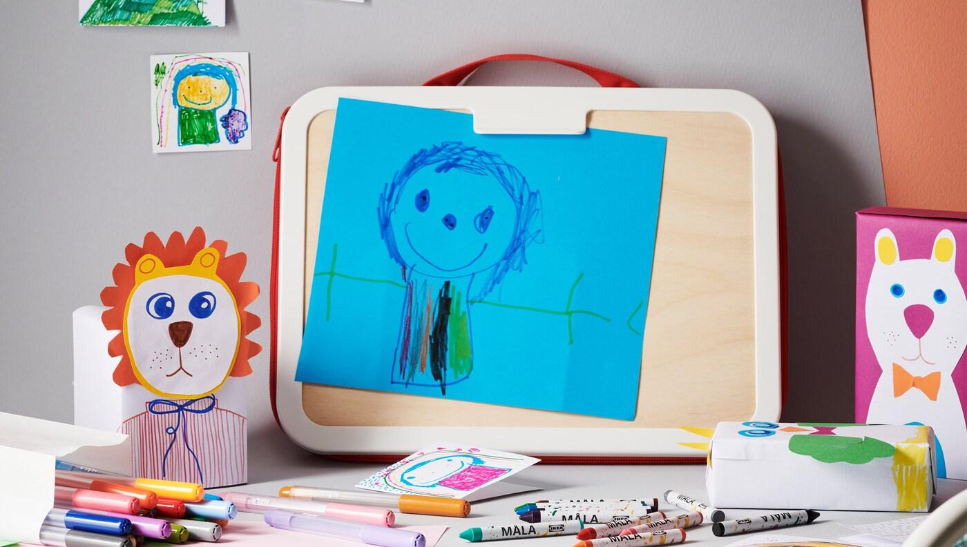 Pöydällä lasten piirroksia ja paljon erilaisia liituja ja kyniä.