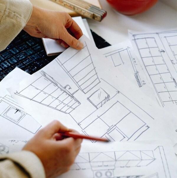 Pöydällä on paljon suunnitelmapiirustuksia. Piirustusten yllä on kädet joista toinen pitää kiinni yhden piirustuksen yläkulmasta ja toisessa on kynä.