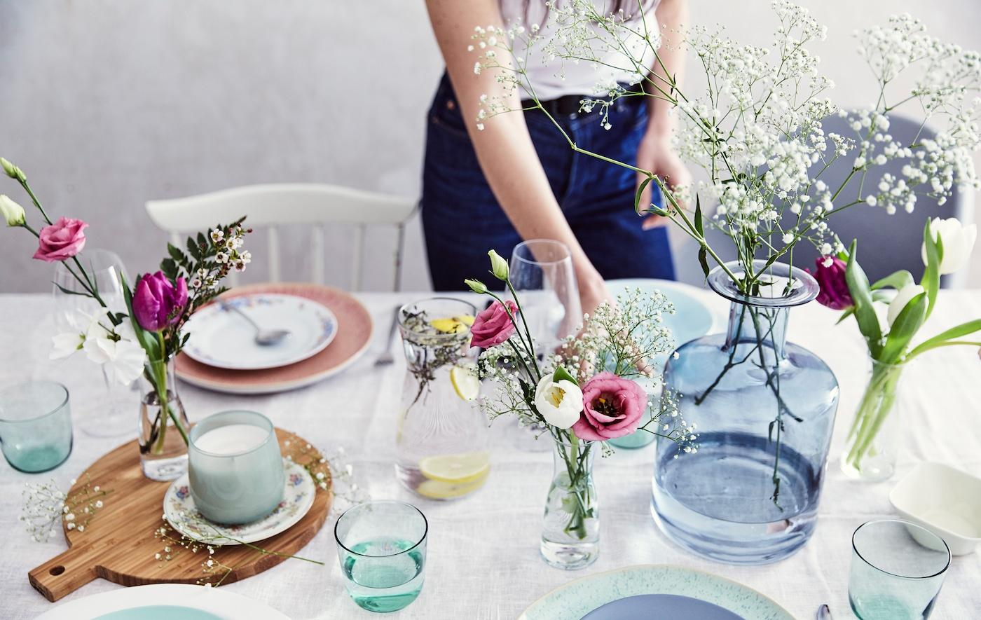 Pöytä, jolla on pastellivärisiä astioita ja tuoreita kukkia, eri muotoisia ja kokoisia lasimaljakoita, puinen leikkuulauta ja puuvilla pöytäliina.
