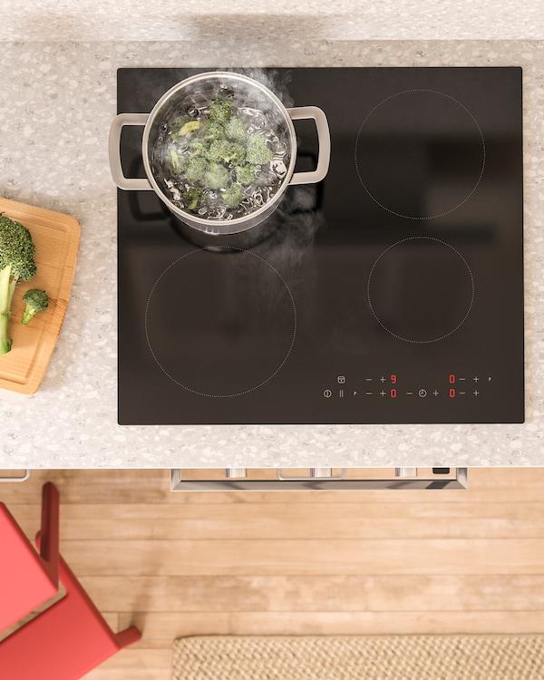 Pogled iz vazduha na MATMÄSSIG crnu indukcijsku ploču, tiganj na njoj i brokoli koji se kuva.
