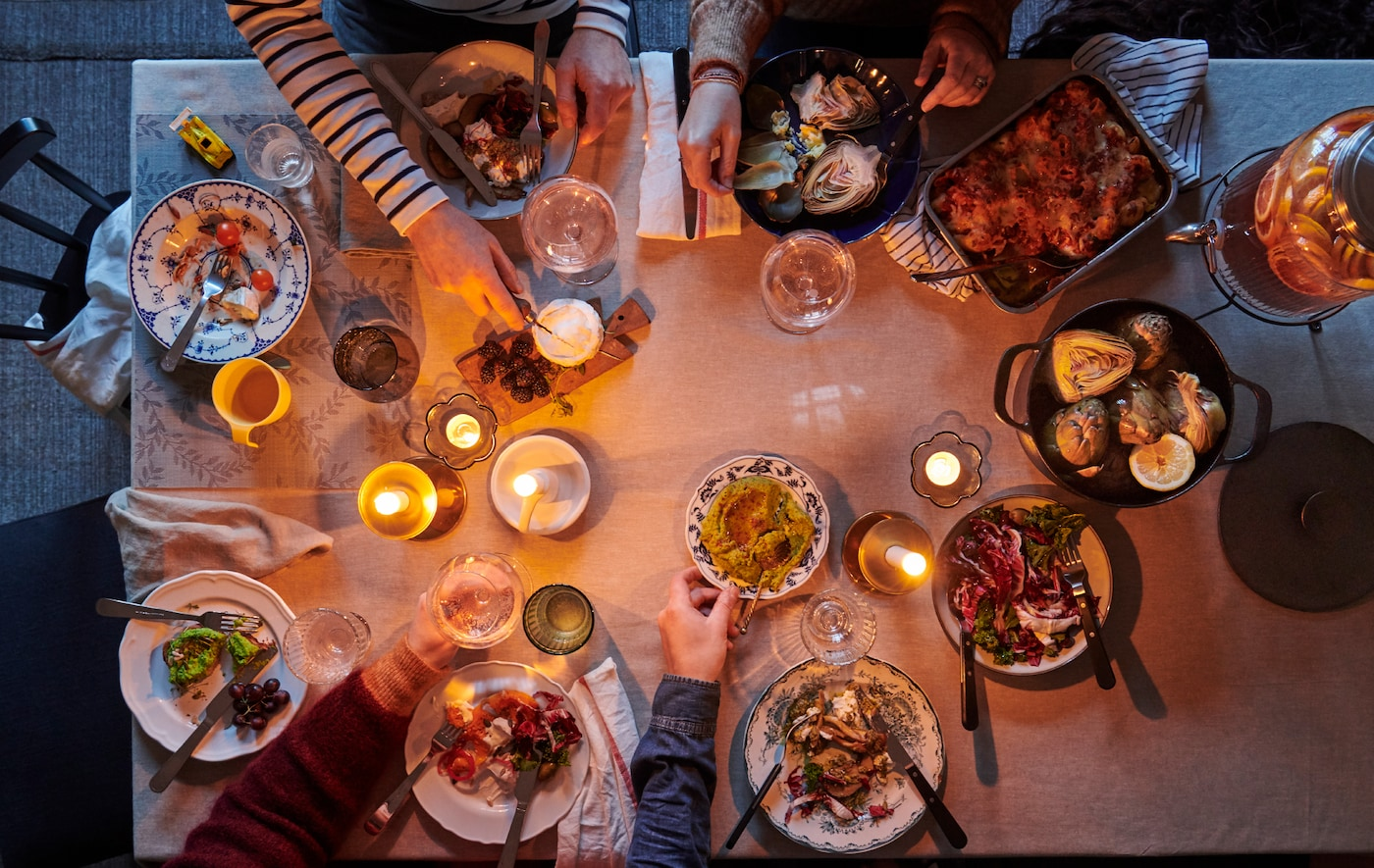 Pogled na trpezarijski sto, postavljen monohromatskim stolnjakom i neformalnom kombinacijom posuđa, tekstila i sveća.