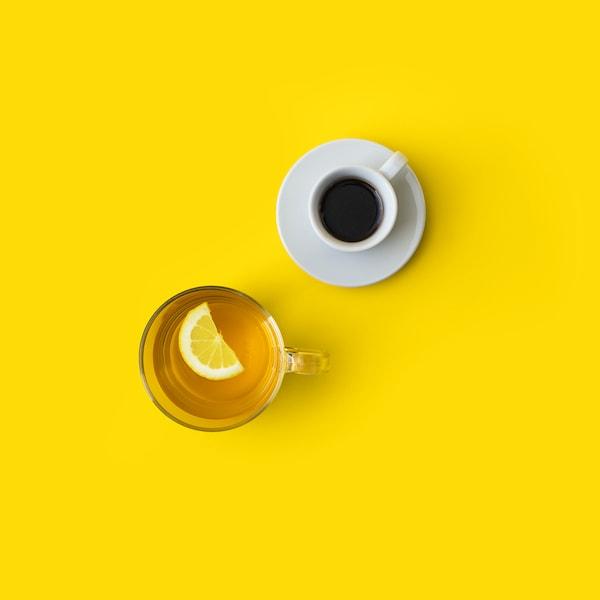 Pohled shora na šálek s kávou a hrnek s čajem a citrónem na žlutém pozadí.