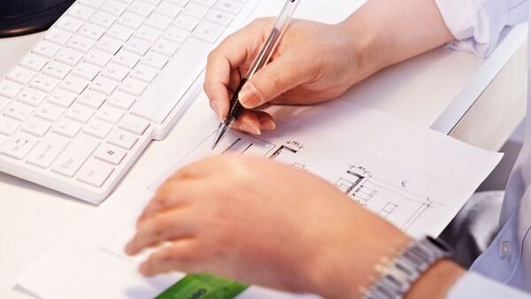 Pohled shora na stůl a klávesnici, před ní jsou vidět ruce pracovníka, který kreslí půdorys místnosti