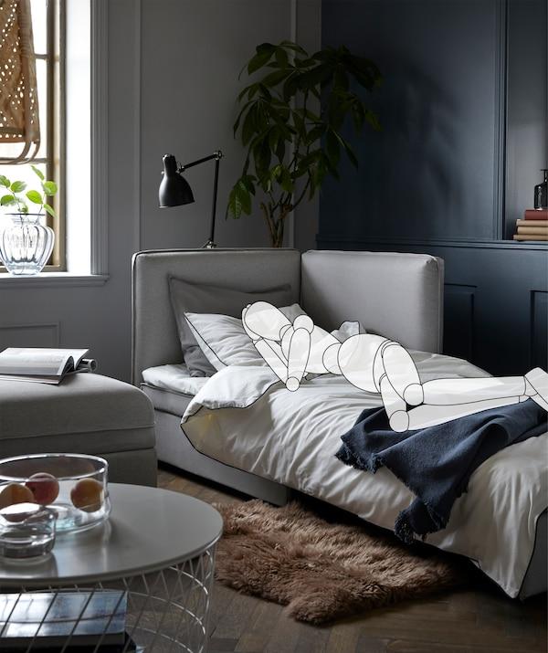 Pohovka v obývacím pokoji. Postavička leží na boku s pokrčenýma nohama.