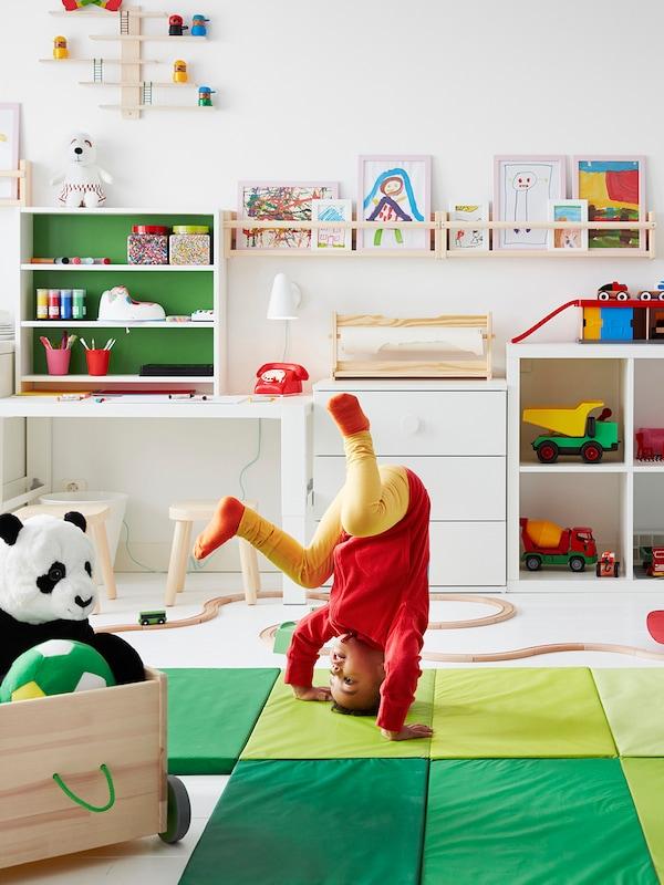 Poika heittää kuperkeikkaa jumppamatolla lastenhuoneessaa, jossa on työpiste ja paljon leluja.