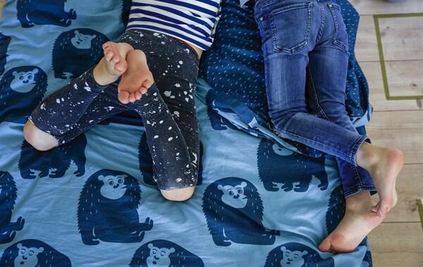 Pojat pötköttelevät sängyssä, jossa siniset, eläinkuvioidut pussilakanat.