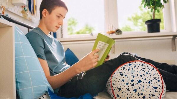 Pojke sitter på golvet och läser en bok med en kudde under och bakom sig