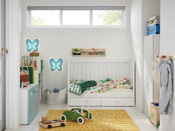 Pokój dziecięcy z białym łóżeczkiem, żółtym dywanem, białą szafą, zielonym wózkiem na zabawki i dwoma niebieskimi lampami ściennymi w kształcie motyla.
