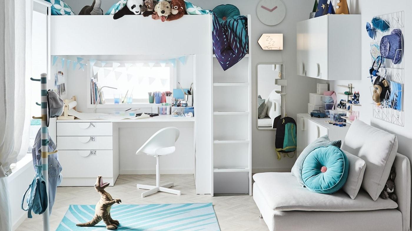 Pokój dziecięcy z białym łóżkiem na antresoli i biurkiem ustawionym pod spodem, turkusowymi akcesoriami i mnóstwem zabawek.