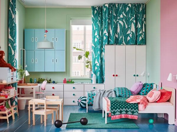 Pokój dziecięcy z białymi szafami i komodami, dwoma rozsuwanymi łóżkami, zielonym dywanem i niebieskimi szafkami ściennymi.