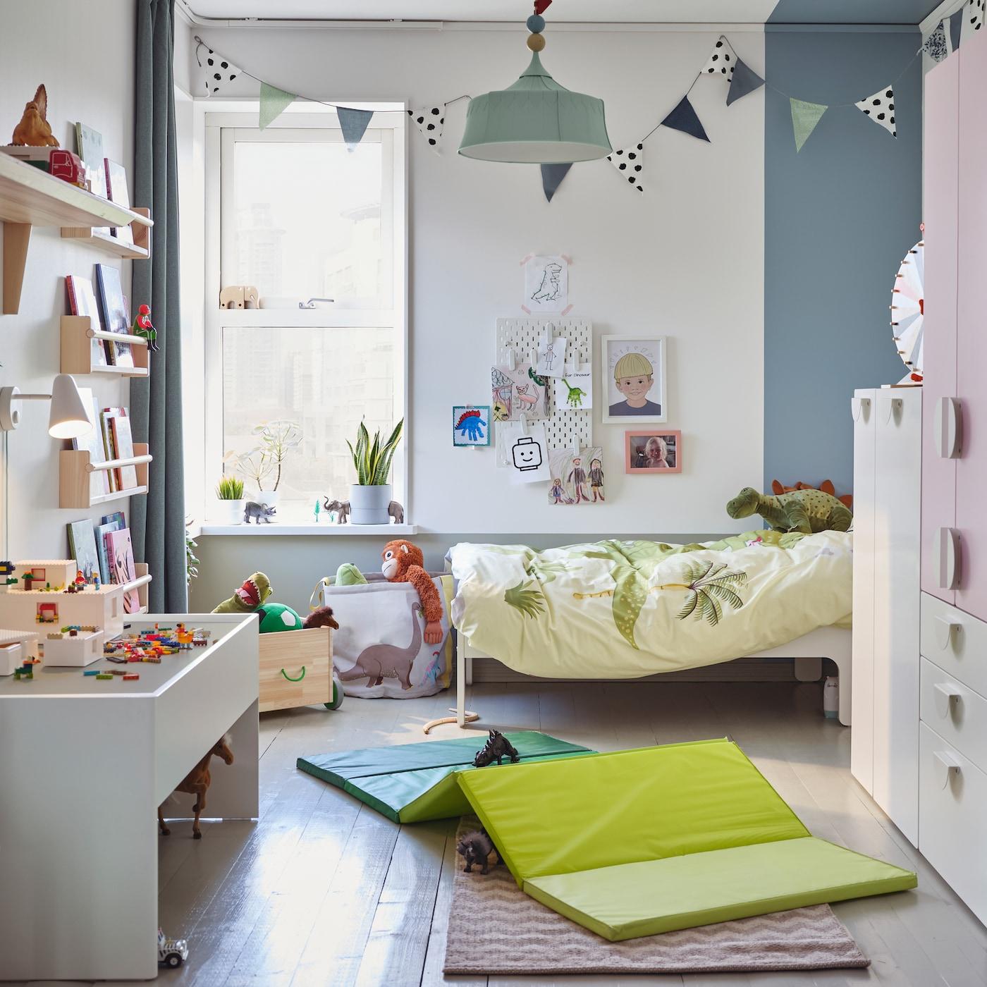 Pokój dziecięcy z szafą w kolorach białym i bladoróżowym, zieloną matą gimnastyczną na podłodze, białym stolikiem do zabaw i pluszowymi dinozaurami.
