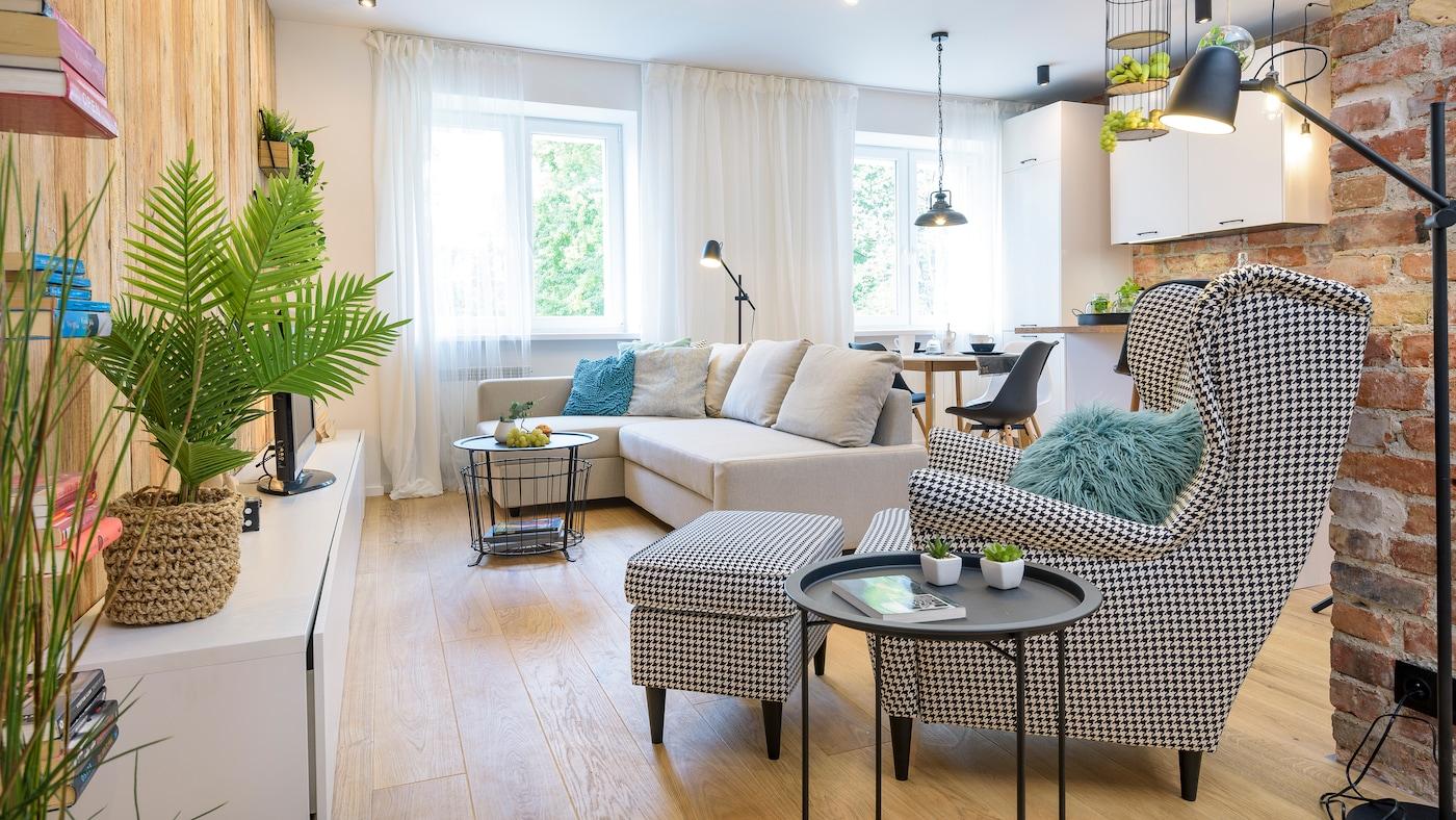 Pokój dzienny jasnego mieszkania, Na pierwszym plnie fotl z podnóżkiem i stolikiem bocznym oraz beżową sofą.