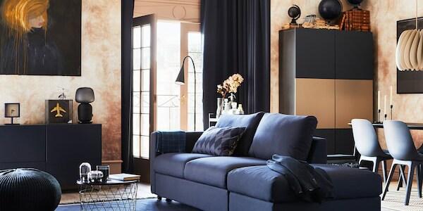 Pokój dzienny z 3-osobową sofą rozkładaną VIMLE i czarno-niebieskim pokryciem ORRSTA, różne szafki, siedziska i otwarte drzwi na patio.