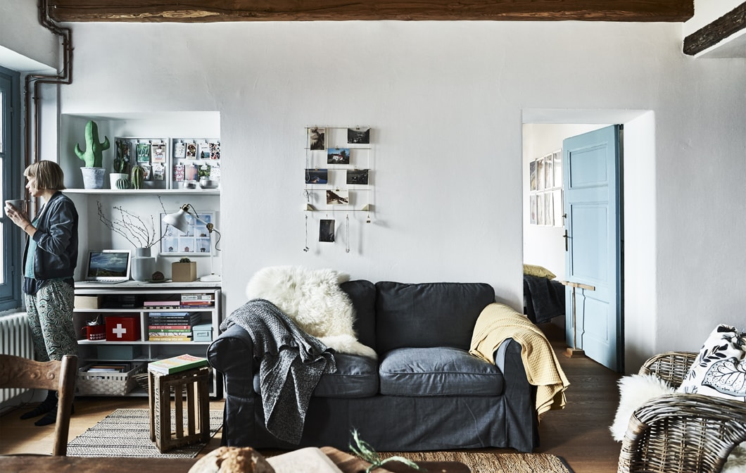 Pokój dzienny z białymi ścianami i szarą sofą.