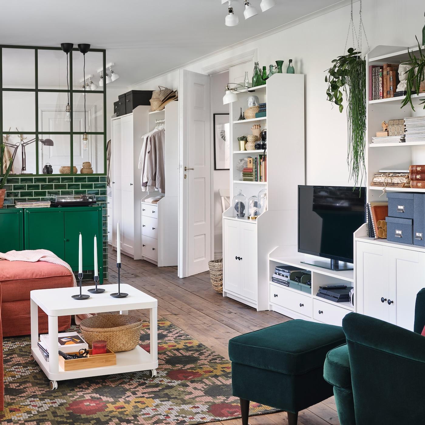 Pokój dzienny z ciemnozielonymi fotelem i podnóżkiem, zielonymi szafkami i białym zestawem do przechowywania HAUGA z szafką pod telewizor.