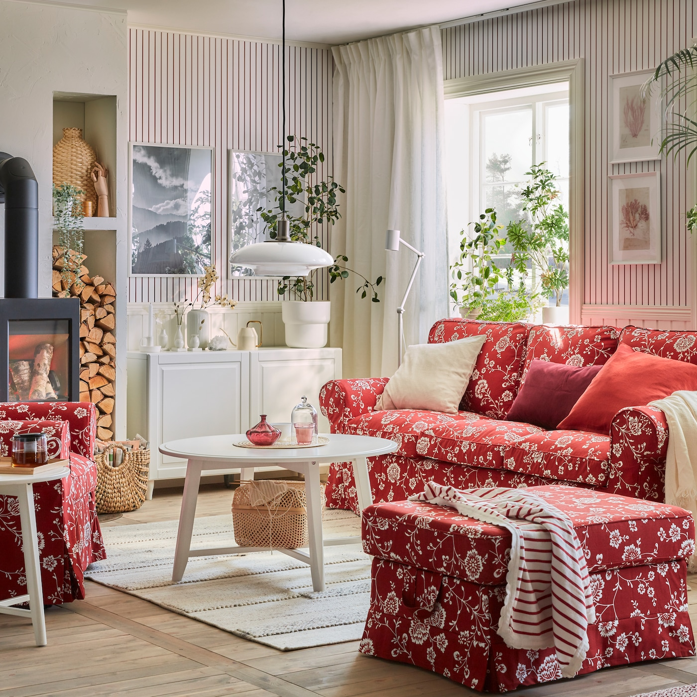 Pokój dzienny z czerwonymi, ozdobionymi białym, kwiecistym wzorem sofą, fotelem i podnóżkiem EKTORP oraz okrągłymi stolikami i kredensem w kolorze białym.