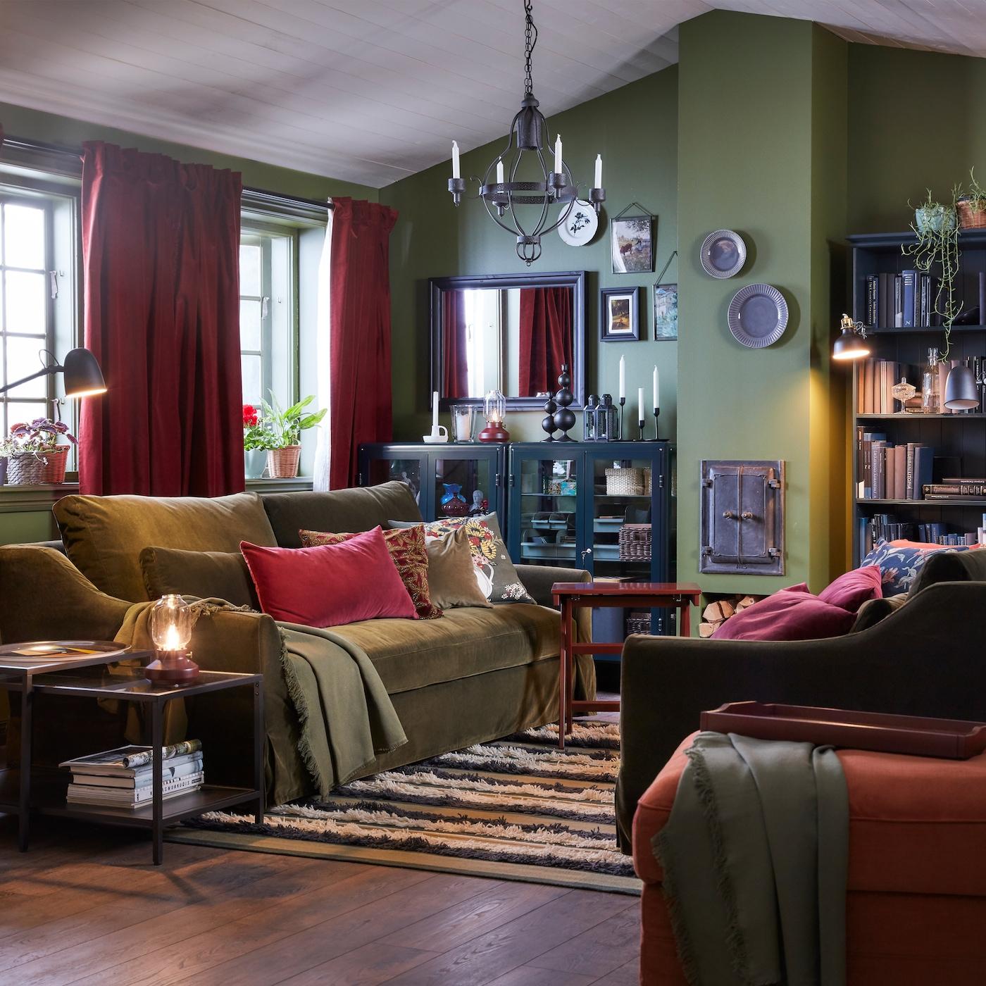 Pokój dzienny z dwoma oliwkowozielonymi sofami, jasnoczerwonym podnóżkiem, czarnym żyrandolem, czerwonobrązowymi zasłonami i pasiastym dywanem.