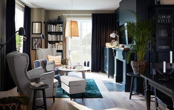 Pokój dzienny z dwoma wysokimi fotelami w pepitkę, zielonym dywanem, bambusową lampą wiszącą i okrągłym stolikiem kawowym.