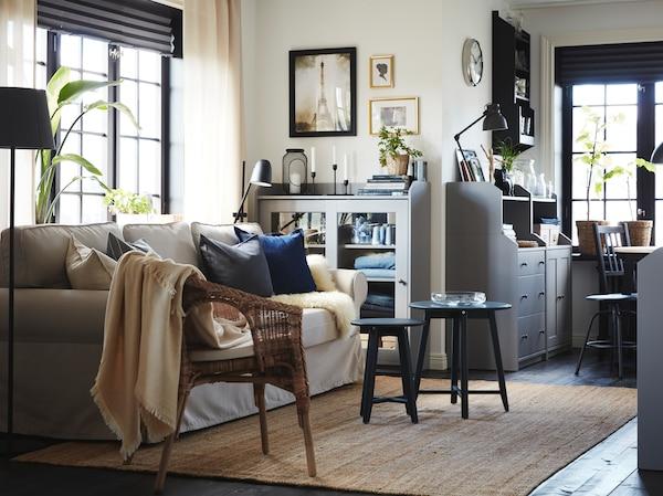 Pokój dzienny z jasnobeżową rozkładaną sofą, jutowym dywanem, rattanowo-bambusowym fotelem oraz dwoma szafkami i komodą w kolorze szarym.