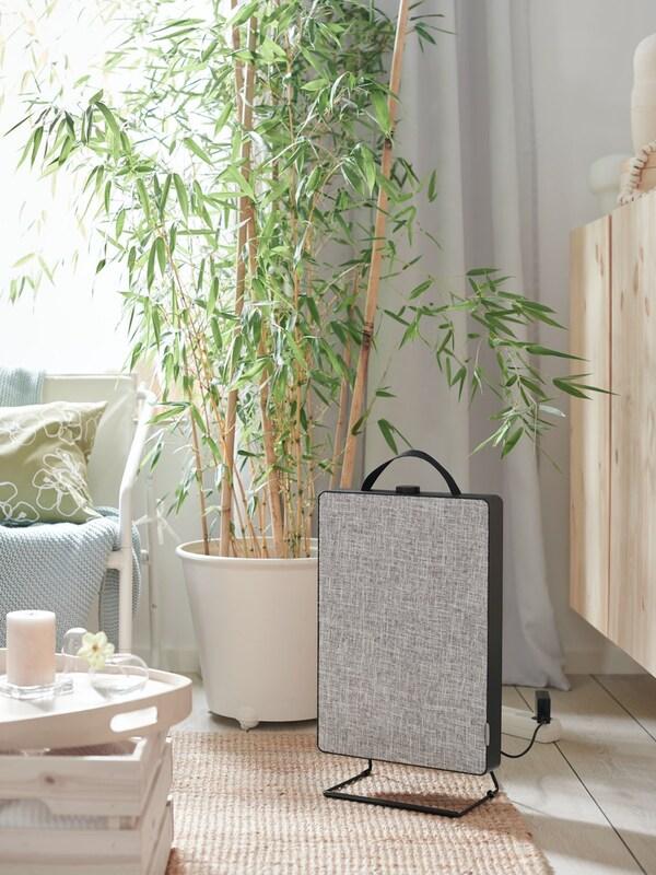 Pokój dzienny z jutowym dywanem, oczyszczaczem powietrza FÖRNUFTIG, białą zasłoną i tacą z bryłową świecą zapachową.