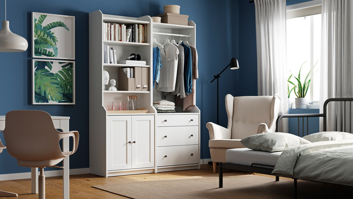 Pokoj s bílou kombinací vysokých skříněk HAUGA, psacím stolem, zarámovanými obrazy, křeslem u okna a rozkládací pohovkou.