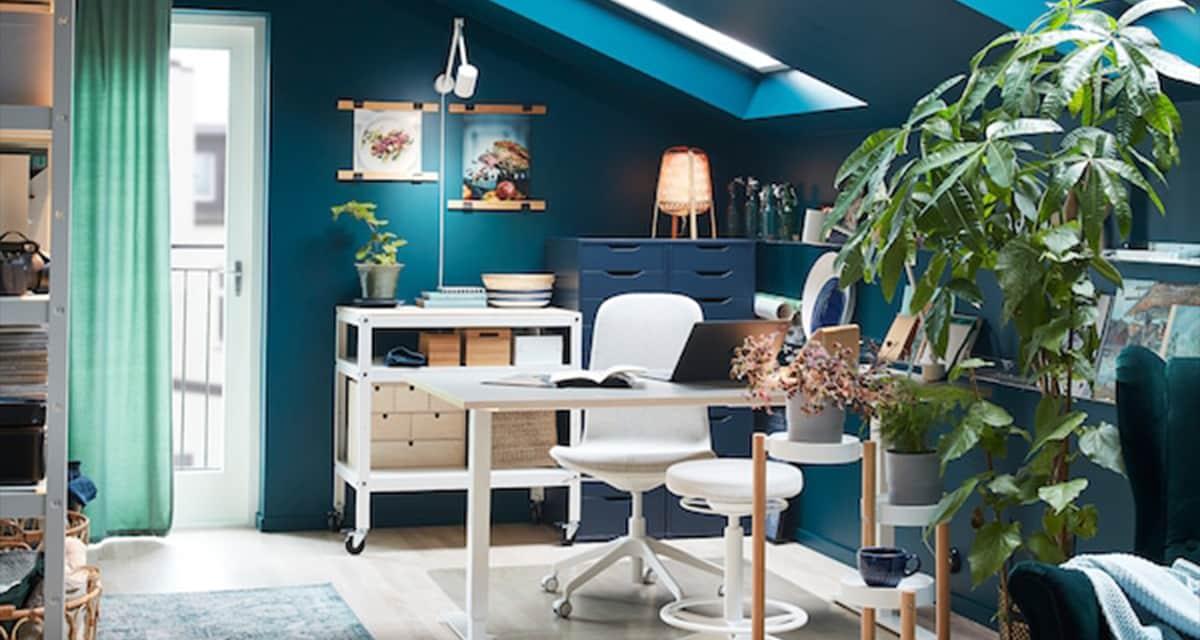 Pokój z biurkiem, krzesłem obrotowym i stołkiem do siedzenia/stania, zielone rośliny na stojaku i zielony fotel uszak.