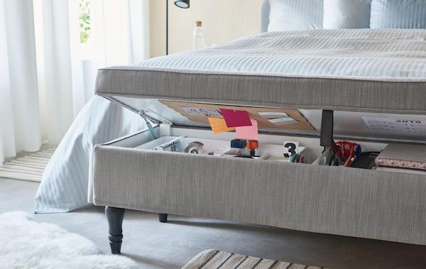 Pokryta tekstyliami uchylona ława ze schowkiem, ustawiona w nogach łóżka z zawartością typową dla domowego biura.