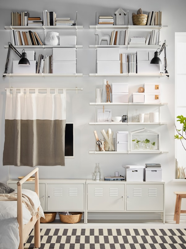 Polițe BERGSHULT/PERSHULT albe, pline cu obiecte de depozitare și obiecte decorative și corpuri IKEA PS albe acoperă un perete al dormitorului.