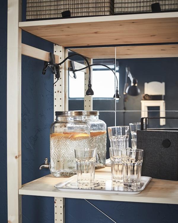Półka drewnianego regału przeznaczona na minibar; wypełnione szklane słoiki z kranikiem, taca ze szklankami, głośnik Bluetooth.