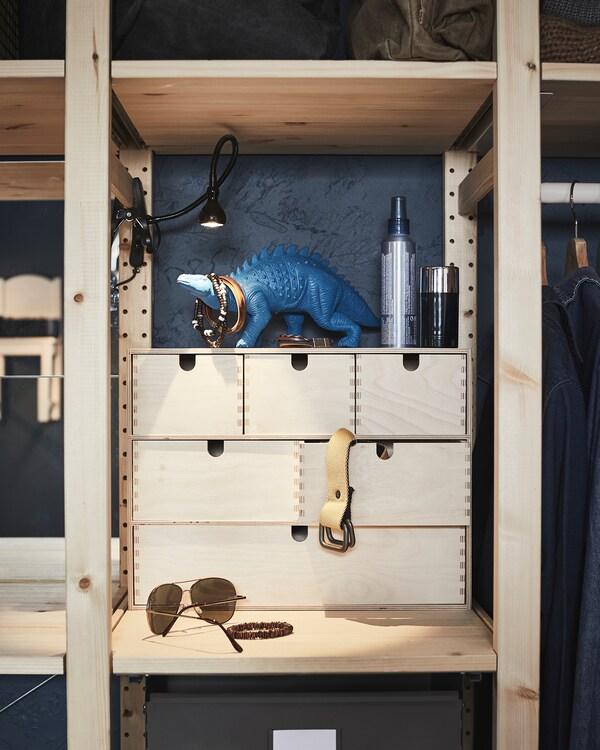 Półka drewnianego regału z mini komodą wypełnioną i otoczoną akcesoriami typowymi dla nastolatka.