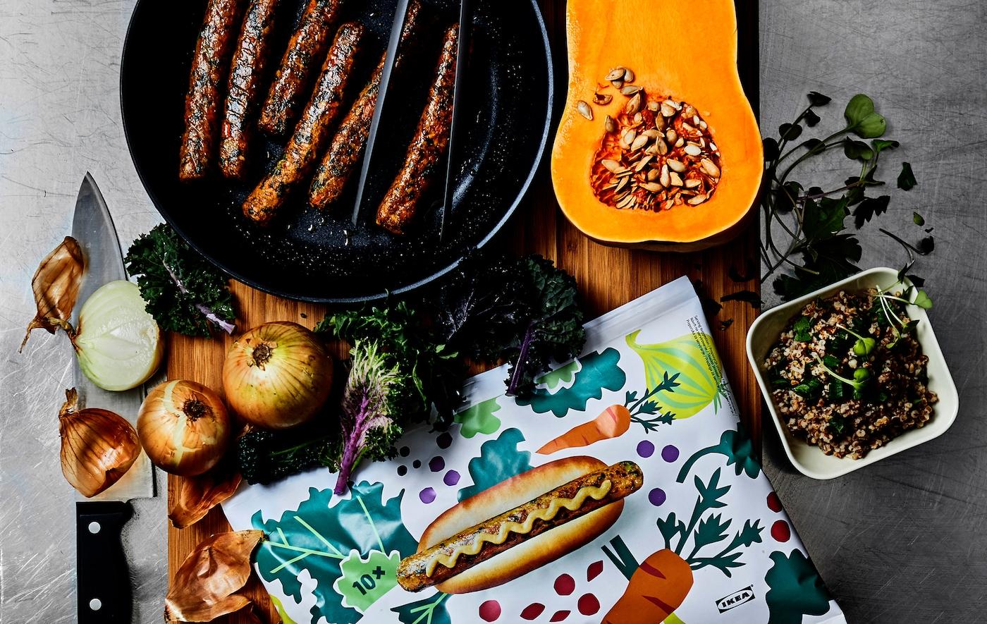 Pølser i ei stekepanne, grønnsaker og ei mønstret pølsepakke på ei trefjøl.