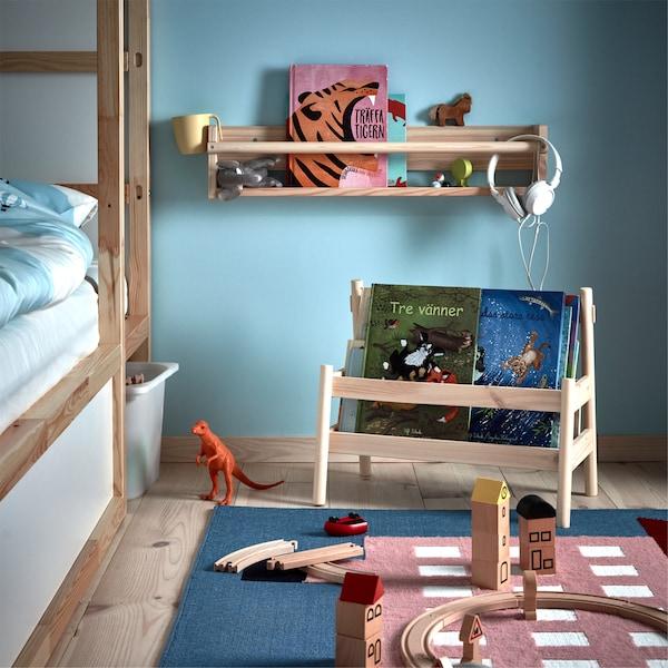 Pored dečjeg kreveta nalaze se FLISAT stalak za knjige i zidni element za odlaganje, puni knjiga i igračaka.